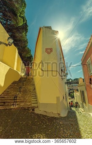 Stairs on the small street at sunny day in old district Alfama. Travel concept. Lisbon, Portugal. Europe