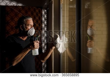 Coronavirus Covid-19 Home Safety Concept, Middle Aged Man In Protective Medical Mask Sterilizing And
