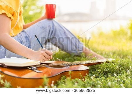 Female's Hand Writing Music Notes On Book. Concept Of The Music Creating, Composing, Note Writing, M