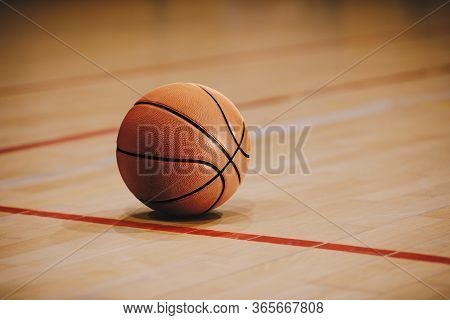 Classic Basketball On Wooden Court Floor Close Up With Blurred Arena In Background. Orange Ball On A