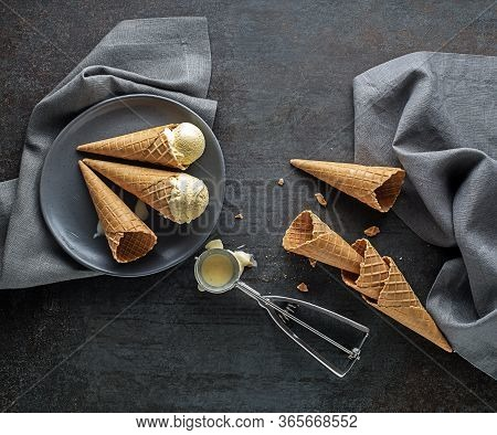 Vanilla Ice Cream Scoops, Scooped From Container In To Waffle Cones With A Silver Utensil