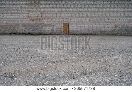 Lonely Wooden Door On Brick Wall. Conceptual Background