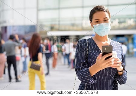 Young Asian Businesswoman With Mask Using Phone While Having Coffee On The Go As The New Normal Duri