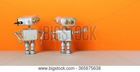 Robot Points Direction To Second Robot. Two Simplified Metal Silver Robotics Toys On Orange Wall, Gr