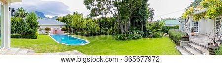 Exterior Of Upmarket Wealthy Suburban Mansion House With Landscaped Garden And Swimming Pool