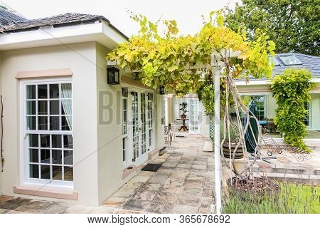 Patio Terrace Of Upmarket Wealthy Suburban Mansion House With Landscaped Garden