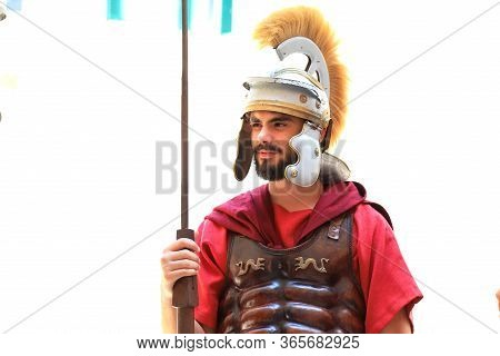 A Young Bearded Man In A Red Uniform Of A Roman Legionary, In A Metal Helmet, Tunic And With A Spear