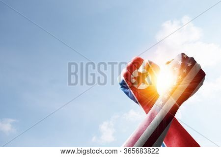 Usa Flag And North Korea Flag Print Screen Fists And Wrestling With Blue Sky And Sunlight. United St