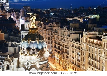MADRID, SPAIN – MAY 13, 2018: Business shopping area at night on Gran Via with historical buildings and traffic.