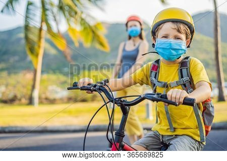 Active School Kid Boy And His Mom In Medical Mask And Safety Helmet Riding A Bike With Backpack On S