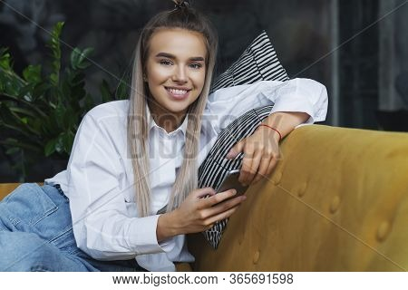 Pretty Girl Sitting On Sofa, Playing Mobile Games On Smartphone. Entertainment Video Content On Port
