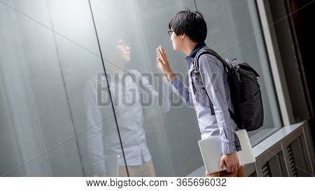 Young Asian Man Carrying Bag And Laptop Computer Looking At Himself Touching On Glass Window While R