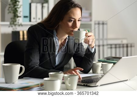 Executive Woman Overworking Needing Caffeine Having Several Cups Of Coffee Sitting On A Desk At Nigh