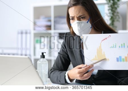 Worried Executive Woman Wearing Protective Mask Shows Bad Results Report On Videocall On Laptop Afte