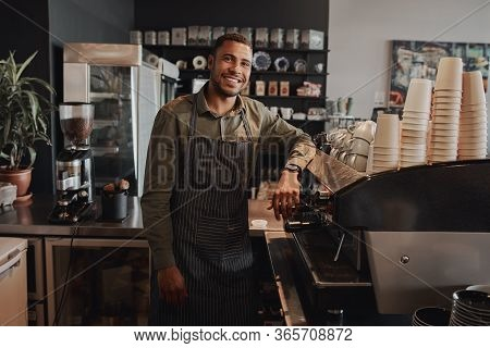 Successful Afro-american Male Business Owner Behind The Counter Of A Coffee Shop Leaning At Counter