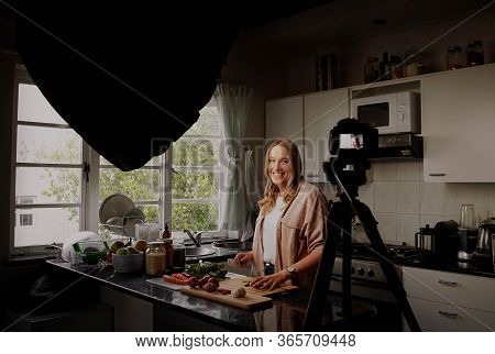 Cheerful Female Food Blogger Recording Video For Vlog At Camera While Standing In Modern Kitchen And