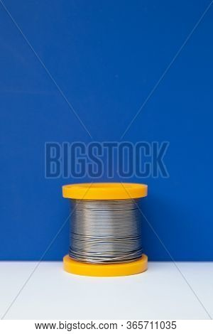 A Yellow Coil Of Solder Stands In The Frame. The Coil Stands On The White And Blue Media Section. So