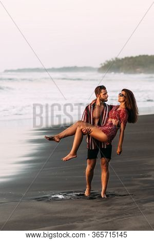 The Couple Is Having Fun On The Beach. A Couple In Love At Sunset Walking Along The Beach. The Man L