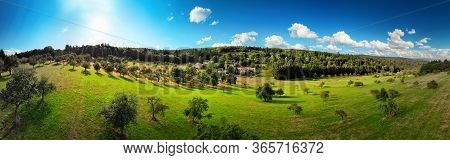 Wide Aerial Panorama View Of A Nice Rural Landscape With Green Meadows On Hills, Trees And A Few Hou
