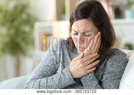 Middle Age Woman In Pain Suffering Toothache Touching Face Sitting On A Couch At Home