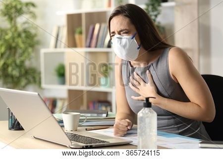 Entrepreneur Woman With Mask Due Covid-19 In Pain Wheezing Sitting On A Desk At Homeoffice