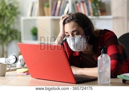 Bored Student Woman With Mask Looking At Laptop Sitting On A Desk In Coronavirus Confinement At Home