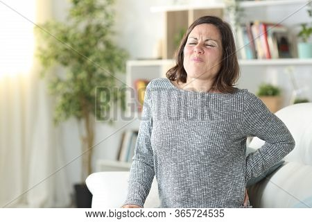 Adult Woman In Pain Complaining Suffering Backache Sitting On A Couch At Home