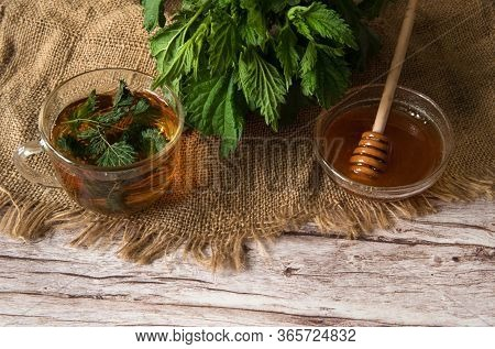 Herbal Tea From Nettle Dioecious With Honey Close-up On A Wooden Background. Alternative Medicine, M