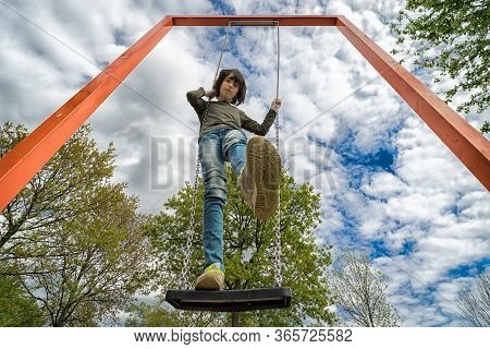 A Boy Stands On A Swing. View From Below. Distortion Of An Ultra Wide Angle Lens.
