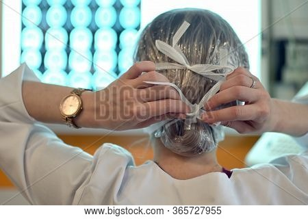 Young Woman Doctor Puts On A Protective Mask