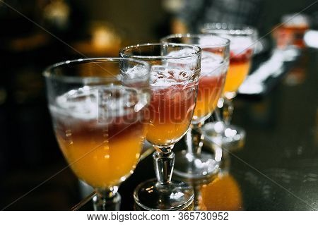 Multicolored Cocktails Are On The Tray. Several Alcoholic Cocktails Are On The Tray. On The Table Ar