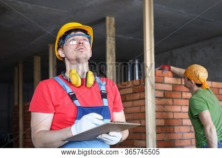 Builder In Overalls And Helmet Makes Notes Folder. Brick Specifications. Builder Calculates Height U