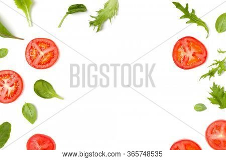Creative layout made of tomato slices and lettuce salad leaves. Flat lay, top view. Food concept. Vegetables isolated on white background. Food ingredients pattern with copy space.