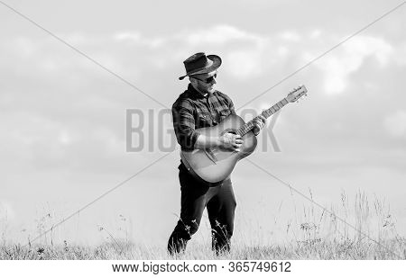 Play Beautiful Melody. Country Music Concept. Guitarist Country Singer Stand In Field Sky Background