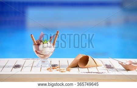 Glass With Mint Ice Cream Scoops On Blur Bokeh Background With Copy Space. Waffle Cones On White Tab