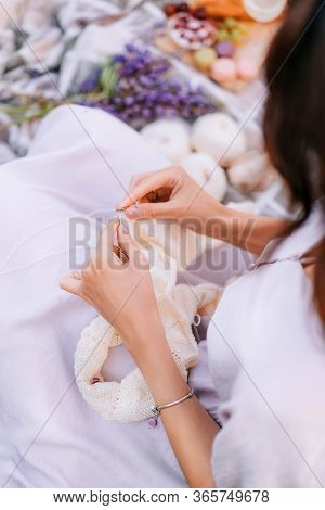 Hands Close-up Knitting On Knitting Needles, White Milk Wool Knit During A Picnic. Needlework In The