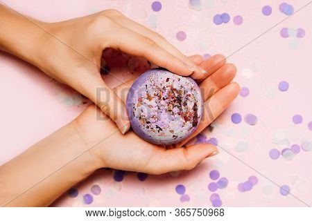 Flat Lay Composition With Bath Bombs In Girls Hand On Pink Background With Festive Confetti.