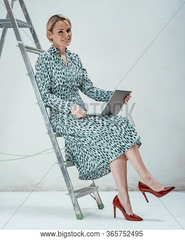 Elegant Business Woman With Short Blonde Hair Sitting On A Stepladder In A Bright Studio, Wearing Ca