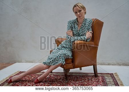 Serious And Bold Adult Woman With Short Blond Hair Posing On A Grey Background While Wearing Colourf