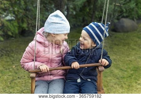 Two Cute Adorable Playful Caucasian Siblings Boy Girl Child Enjoy Having Fun Swinging Wooden Swing A