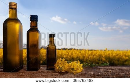 Rapeseed Oil (rapeseed) And Rapeseed Flowers On A Wooden Board. Rapeseed Field Outside - A Few Bottl