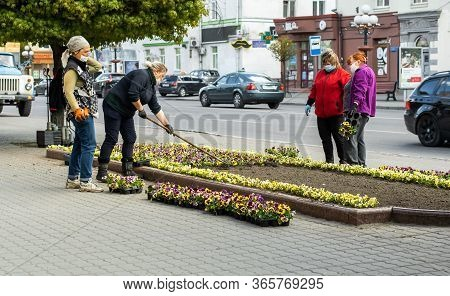 Lutsk, Ukraine - May 11,2020: Flower Gardeners At Work Wear Protective Mask On A Public Street Durin