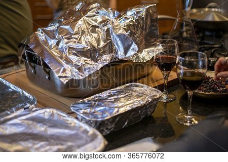 Various Food Dishes Covered In Tin Foil At A Party Or Thanksgiving