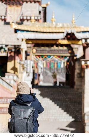 Young Man Traveler With Sweater And Backpack Traveling In Songzanlin Temple, Happy Photographer Taki