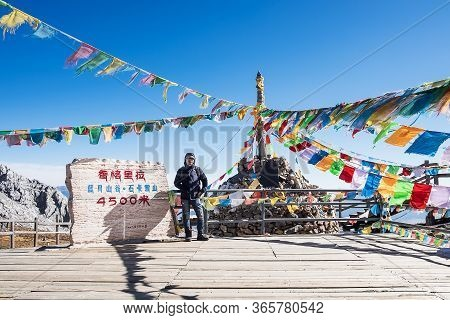 Young Man Traveler Traveling At Shika Snow Mountain Or Blue Moon Valley In Zhongdian City (shangri-l