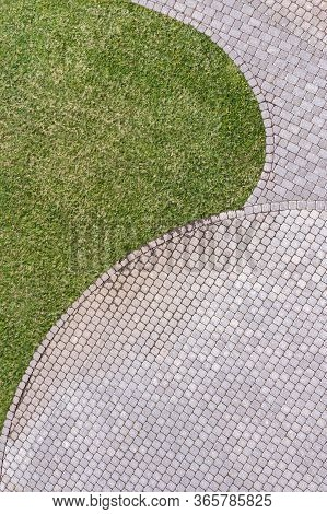Top View Of Gray Cobblestone Pavement Footpath With Green Grass Texture Around Stones