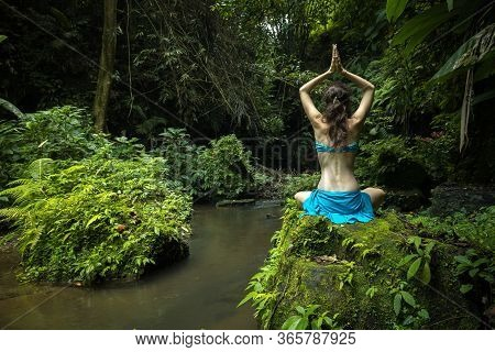 Young Caucasian Woman Sitting On The Rock, Practicing Yoga And Pranayama. Raising Arms With Namaste
