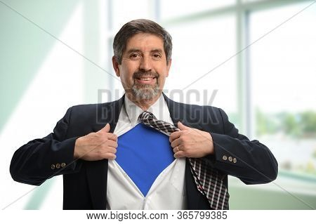 Mature businessman opening up his shirt to reveal his blue  undergarment