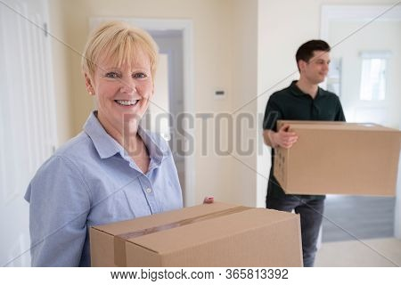 Portrait Of Senior Woman Downsizing In Retirement Carrying Boxes Into New Home On Moving Day With Re