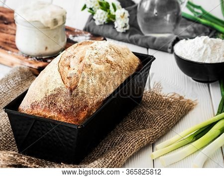 Freshly Baked Bread In A Baking Dish, Sourdough And Flour With A Jug Of Water On A White Wooden Tabl